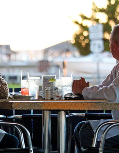A couple sits on the patio of South Beach Grill at sunset