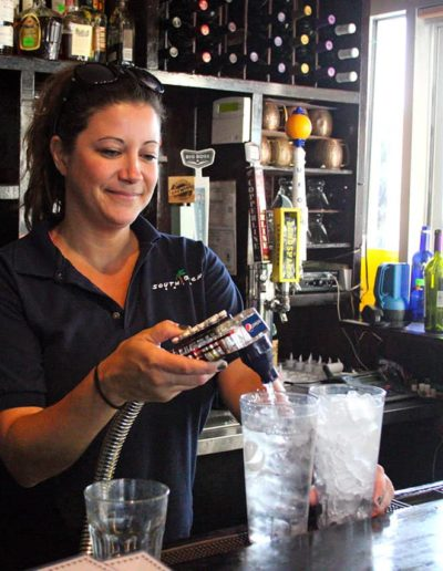 Bar tender pouring glasses of water and on tap craft beer at South Beach Grill