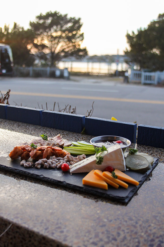 South Beach Grill Sea-cuterie shareable lunch plate being served on outdoor patio at sunset